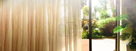 热带景观背景。暑假、旅游、度假和度假的概念。打开窗口, 门和白色窗帘与模糊的棕榈园景观从酒店。异国情调的植物在阳光明媚的日子里复制空间。旗帜