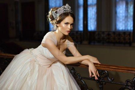 漂亮的黑发女孩穿白色连衣裙,与辉煌的乌鸦
