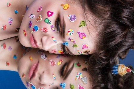 美丽的时尚女孩豪华专业化妆和滑稽表情贴纸粘在脸上。蛋糕在手中的年轻女子