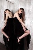 年輕的女孩,與美麗的長頭發和煙熏眼穿著黑色長裙晚禮服擺了一面鏡子。工作室拍攝