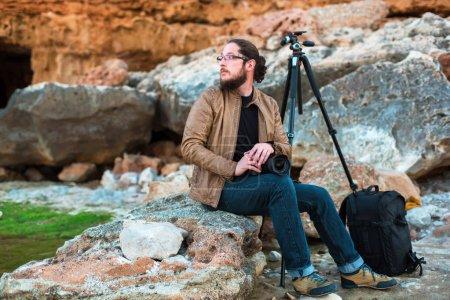 年轻时尚的专业摄影师与胡子和眼镜坐在岩石上, 看着海上相机在手。三脚架和背包在他身旁._高清图片_邑石网