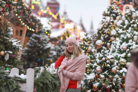 新年那天,街上的一个女人,戴着粉色围巾,背靠一棵装饰过的圣诞树_高清图片_邑石网