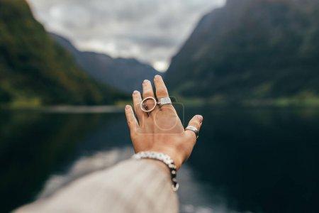 妇女在挪威峡湾。手在自然和湖