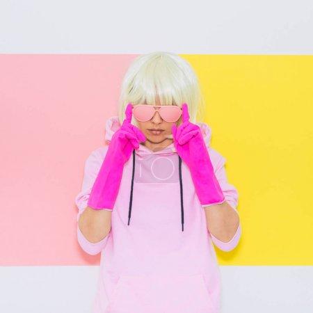 金发女郎模特与美丽的脸在时尚配件太阳镜, 手套, 帽衫和短裤。俱乐部 Dj 聚会的乐趣。情绪和共鸣。最小的独角兽风格。粉红色和黄色的霓虹灯颜色。90s 或80s 趋势_高清图片_邑石网