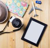 在夏天度假主题的空白图片框。旅行者设备与空相框木制的桌子上