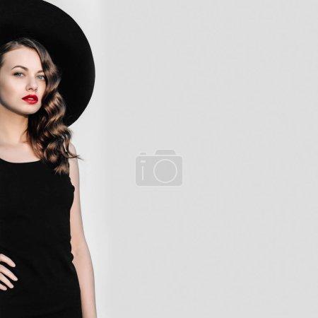高时尚户外全长幅画像,优雅的女人,在黑色的帽子和衣服站在白色柱子后面。黑色与红色的嘴唇女子复古风格肖像._高清图片_邑石网