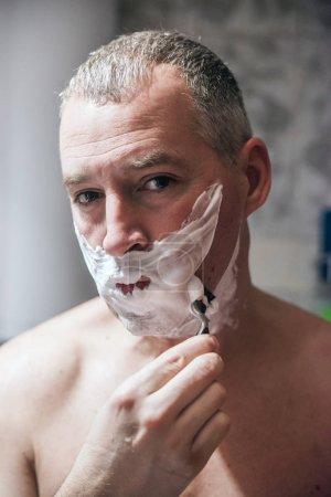 剃掉他的脸上,准备一天的人。英俊的年轻男子是剃掉他的脸上,看着镜子._高清图片_邑石网