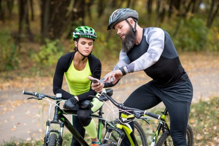 Bearded man showing smartphone to girl
