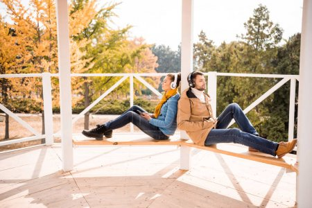 Young couple sitting on bench in headphones
