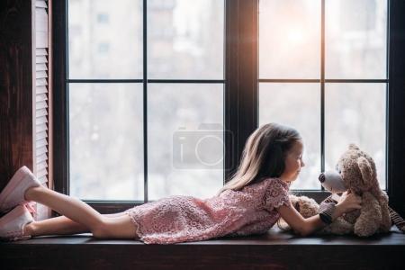 躺在窗台上的小孩子玩泰迪熊的侧面图