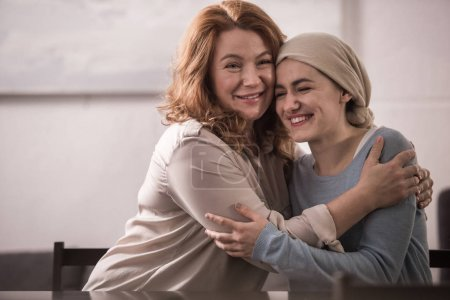 happy mother and sick adult daughter in kerchief hugging and smiling together