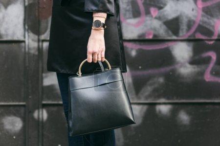 街头的风格,时尚的女人穿黑丝露肩裙,黑色和金色手表和黑色时尚手袋。完美秋季服装细节
