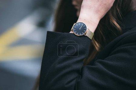 年轻的商界女人穿着金色和黑色的手表和黑色外套。理想的秋天的衣服配件